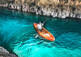 While Sea Kayaking in Arrábida Natural Park from Sesimbra wit Meira Pro Center Sesimbra, a participant is exploring the magical sea caves of the coast with his kayak.