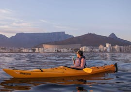 A young woman is enjoying the view of the Cape Town Stadium and Table Mountain behind it while Sea Kayaking in Cape Town with Gravity Adventures.