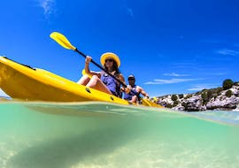 A couple is paddling across the turquoise waters of the Langebaan Lagoon while Sea Kayaking in West Coast National Park with Gravity Adventures.