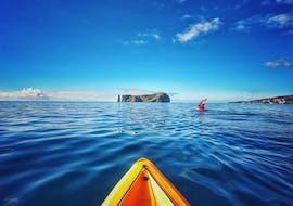 Lors de l'excursion en Kayak de mer autour de l'îlot Vila Franca do Campo avec Fun Activities Azores Adventures, un kayakiste se dirige vers l'îlot sur la mer claire et bleue.