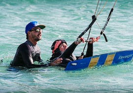 A customer of Addict kite school is practising Semi-Private Kitesurfing Lessons for All levels in the water with his instructor of in Tarifa.