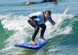A young girl from the Gecko Surf School surfs on the Costa da Caparica.