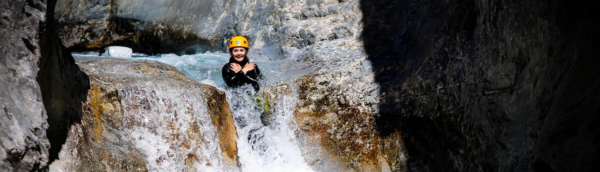 A woman is sliding down a natural slide during a canyoning tour with SerreChe Canyon.