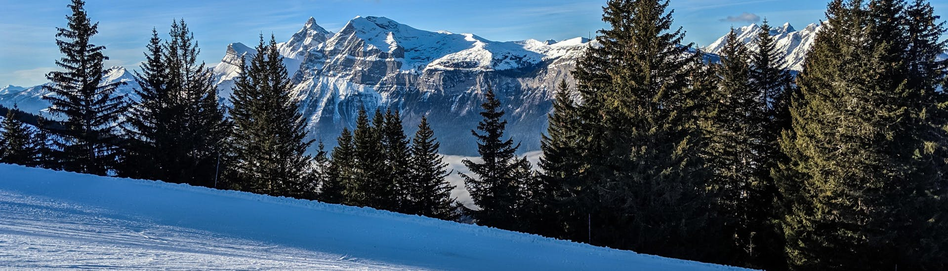 An image of a freshly prepared ski slope in the French ski resort of Les Carroz, a popular place to go skiing in the Grand Massif where visitors can book ski lessons with one of the local ski schools.