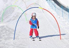 Ein kleines Mädchen läuft im Kinder Skikurs für 4-14 Jahre - Halbtags - Mit Erfahrung an Hindernissen entlang der Skischule Scuola di Sci Azzurra Livigno.