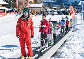 A ski instructor from Outdoor Interlaken is taking the conveyor belt lift with his students during the Adult Ski Lessons for Beginners - Pick-up from Interlaken.
