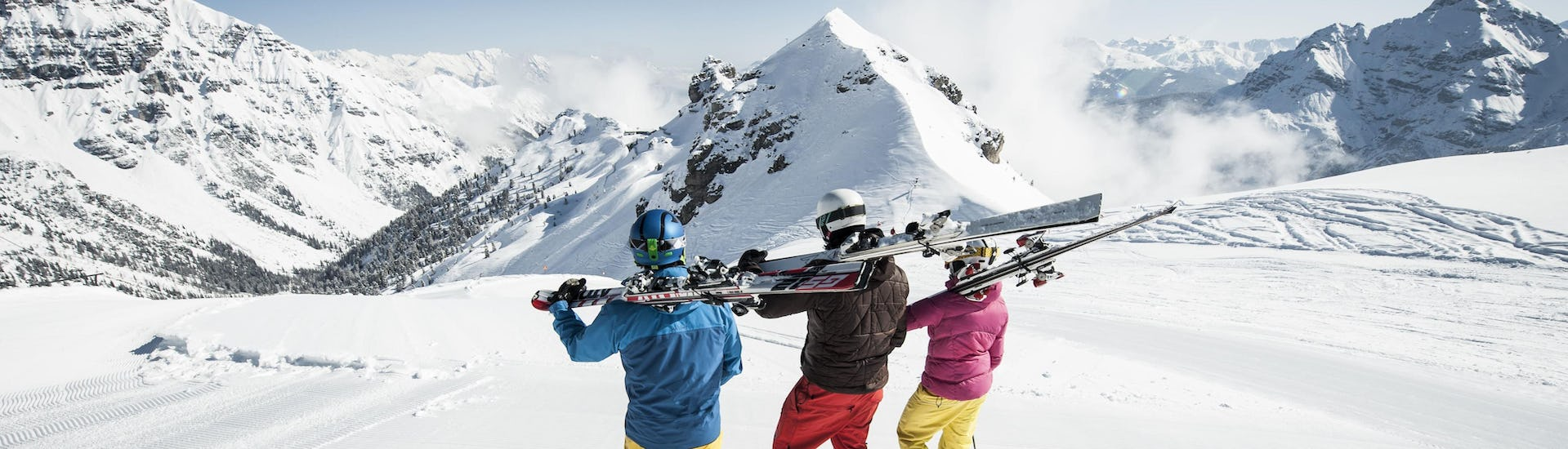 3 skiers prepare for their ski lessons in English in the ski resort of Switzerland.