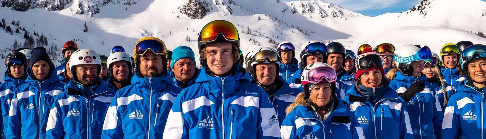 The ski instructors from the ski school Skischule Fieberbrunn Widmann Mountain Sports who teach Ski Lessons for Adults - Beginner are jointly posing for a group photo.