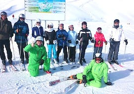 A group of adults with two instructors from Alpin Skischule Oberstdorf are enjoying their break during the Ski Lessons for Adults - Advanced.
