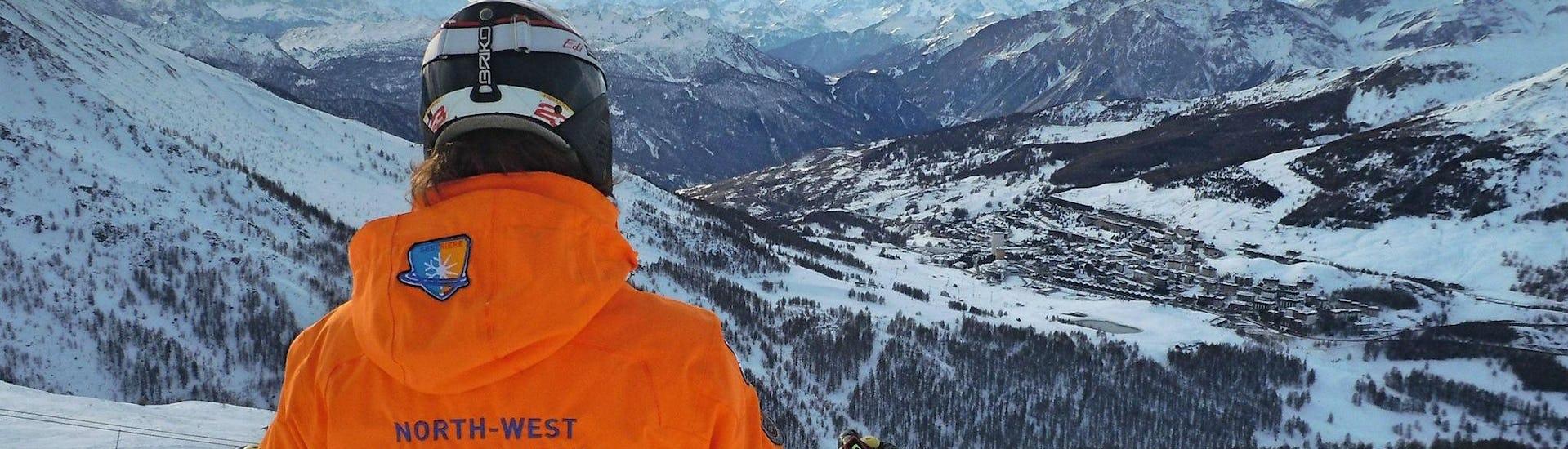 Uno sciatore sta ammirando le cime innevate del comprensorio sciistico di Sestriere durante una delle Lezioni di sci per adulti - Intermedi/Avanzati organizzate dalla scuola di sci YES Academy Sestriere.