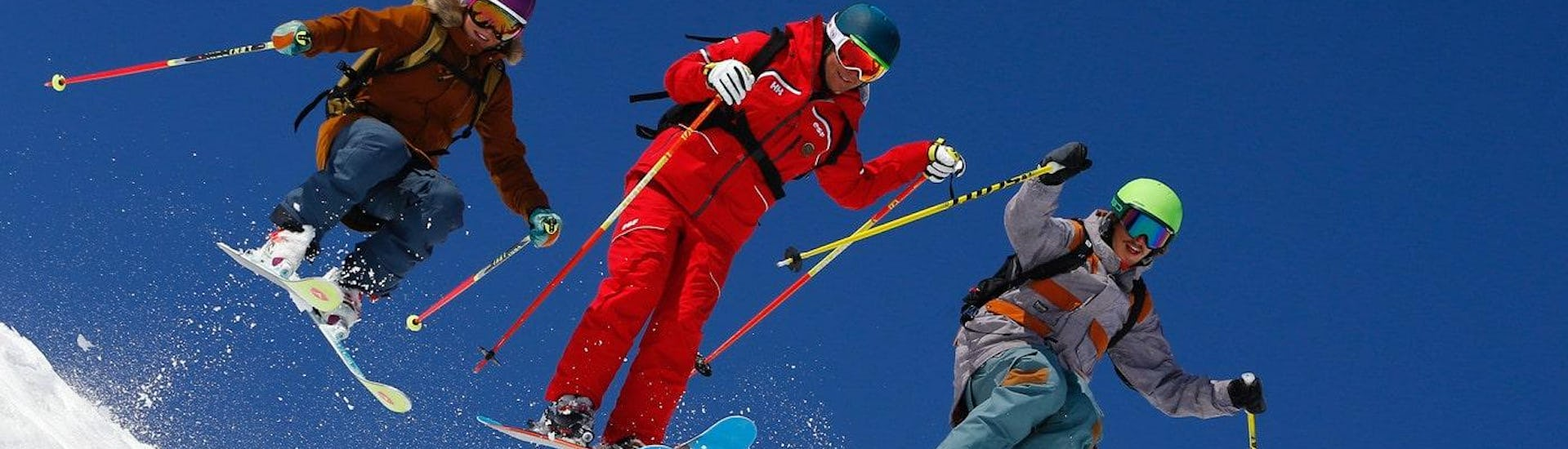 Skiers are skiing with confidence with their ski instructor from the ski school ESF Alpe d'Huez during their Ski Lessons for Adults - All Levels.