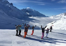 Skiers are standing in line in front of a snow-covered mountain landscape backdrop with their arms in the air during their Ski Lessons for Adults - All Levels with the ski school ESF Chamonix.