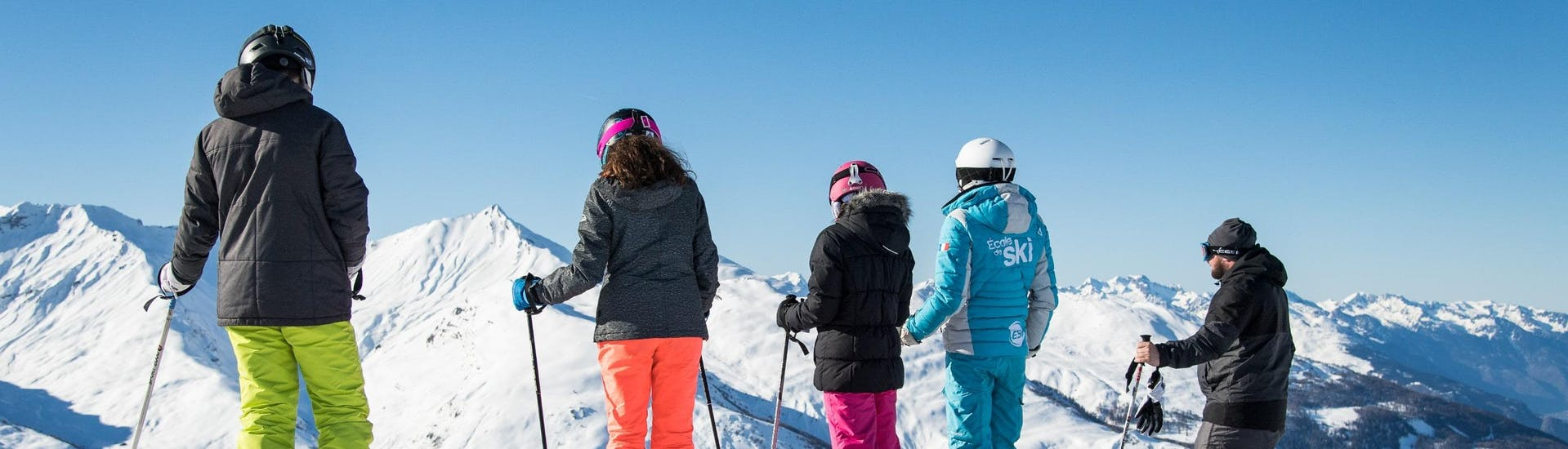 Skiers are looking at a beautiful winter landscape of snow-covered mountains during their Ski Lessons for Adults - All Levels with the ski school ESI Dévoluy.