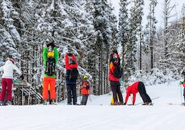 Skiers are stretching in the middle of a forest landscape during their Ski Lessons for Adults - All Levels with the ski school Moonshot La Bresse.