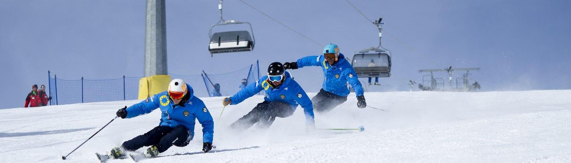 Tre maestri di sci della scuola di sci Scuola di Sci Azzurra Livigno che scendono lungo la pista da sci in formazione durante una delle lezioni di sci per adulti - Tutti i livelli, dimostrando la corretta tecnica sciistica.