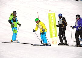 A group of adult skiers practice with the obstacles helped by the ski instructor during the Ski Lessons for Adults - All Levels of the ski school Scuola di Sci e Snowboard Livigno Italy.