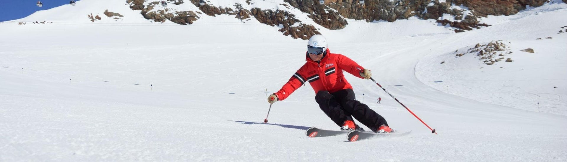 A ski instructor from the ski school Ski- und Snowboardschule Vacancia is demonstrating the correct skiing technique during one of the Ski Lessons for Adults - All Levels.