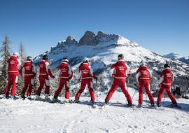 A group of adults is looking at the Dolomites during Ski Lessons for Adults - Beginner from the Carezza Skischool.