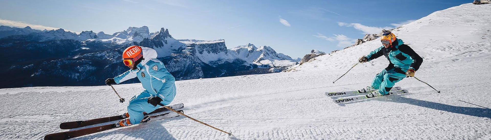 A ski instructor is leading the way down a ski slope in the ski resort of Cortina d'Ampezzo during one of the Ski Lessons for Adults - Beginner organised by the ski school Scuola di Sci e Snowboard Cristallo Cortina.