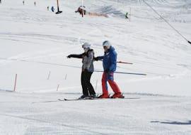 Ein Skilehrer hilft einem Herrn bei den ersten Skifahrten im Skikurs für Erwachsene - Anfänger der Skischule Ischgl Schneesport Akademie.