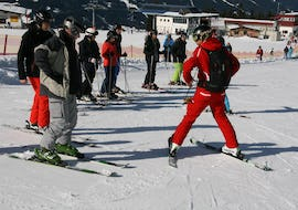 A ski instructor from the ski school Skischule Lechner in Zell am Ziller is showing a group of adults how to ski during their Ski Lessons for Adults - Beginners.