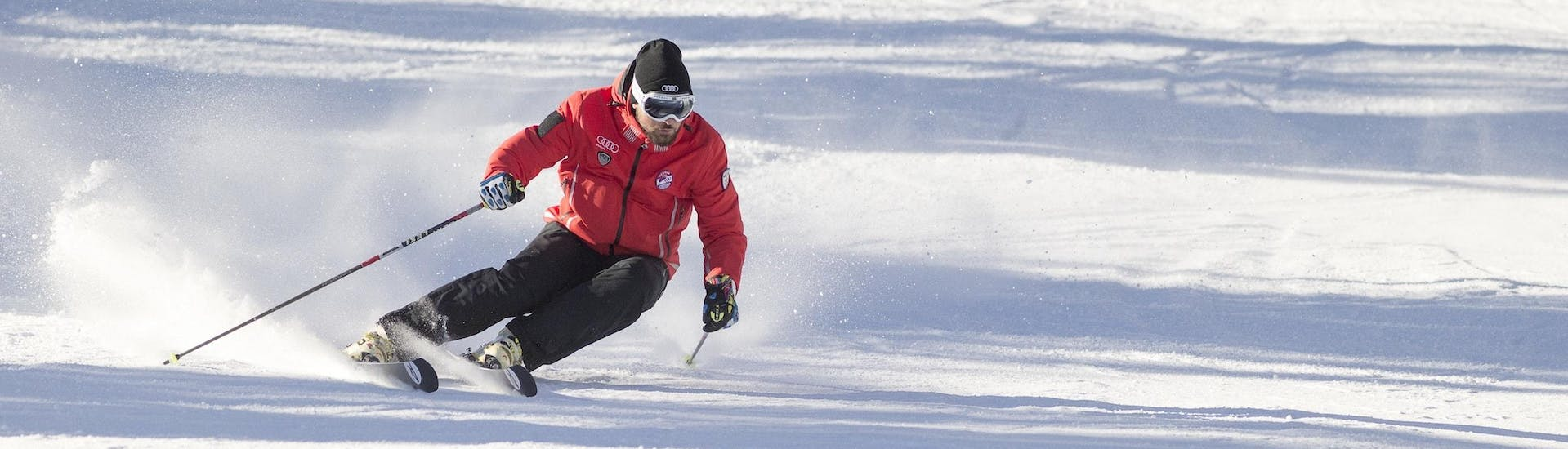 A ski instructor from Scuola Sci Cortina is demonstrating the right skiing technique during one of the Ski Lessons for Adults - First Timer in the ski resort of Cortina d'Ampezzo.
