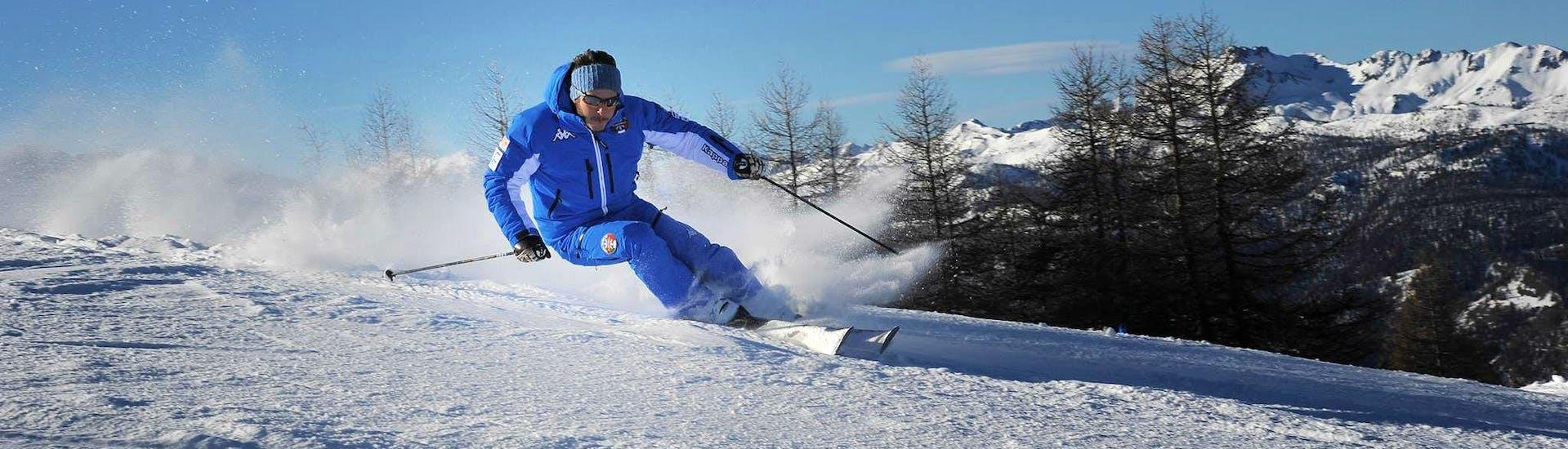 Un maestro della Scuola di Sci Olimpionica a Sestriere sta insegnando la giusta tecnica sciistica durante le Lezioni di sci per adulti - Festività - Con esperienza.