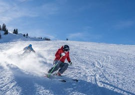 """A ski instructor is demonstrating the right skiing technique during the Private Ski Lessons for Adults """"Lunch Special"""" - All Levels with Swiss Ski School Chäserrugg."""