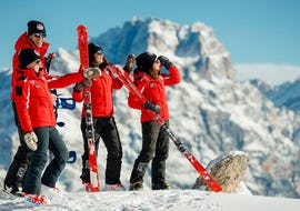 A group of friends on top of a slope are ready to improve their skiing skills during Ski Lessons for Adults - With experience with the ski school Scuola Sci Cortina.