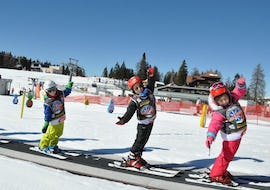 Three kids having fun on the magic carpet during the Ski Lessons for Kids (3-4 years) - First Timers - Holidays organized by the ski school Scuola di Sci Vigo di Fassa.