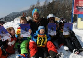 """A ski instructor of the Skischule Semmering having fun with the kids in the snow, after the Kids Ski Lessons """"Bambini"""" (3-5 y.) - Half Day - Holidays."""