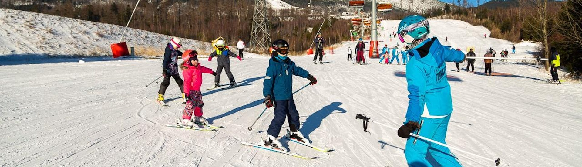 During the Ski Lessons for Kids (from 4 years) - Long Lesson, a group of children is enjoying skiing under the supervision of an experienced ski instructor from the ski school Ternavski Snow Academy Tatranska Lomnica.