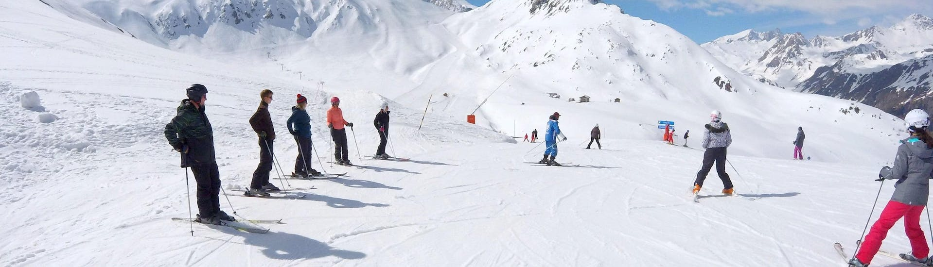 A group of skiers is standing in the middle of a slope waiting for the instructions of their ski instructor from the ski school ESI Valfréjus during their Ski Lessons for Teens & Adults - All Levels.