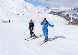 A skier and her ski instructor from the ski school ESI Valfréjus are standing in the middle of a slope during their Ski Lessons for Teens & Adults - All Levels.
