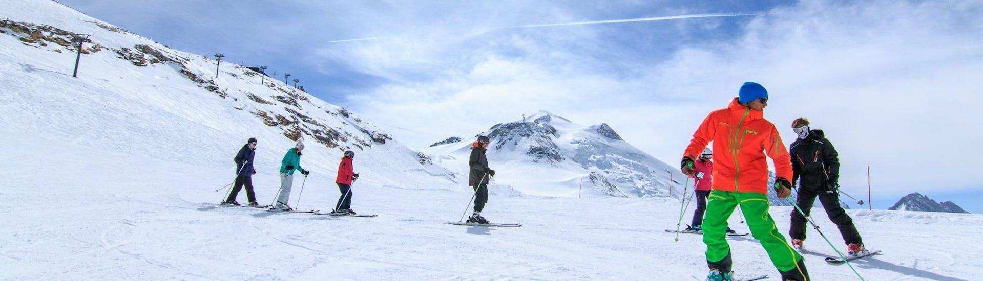 Des skieurs suivent leur moniteur de ski de l'école de ski Evolution 2 Tignes le long d'une pente enneigée pendant leur Cours de ski pour Ados & Adultes - Après-midi.