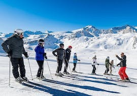 At the top of the slopes a group of skiers is listening to the instructions of their ski instructor from the ski school Evolution 2 Tignes during their Ski Lessons for Teens & Adults - Morning - All Levels.