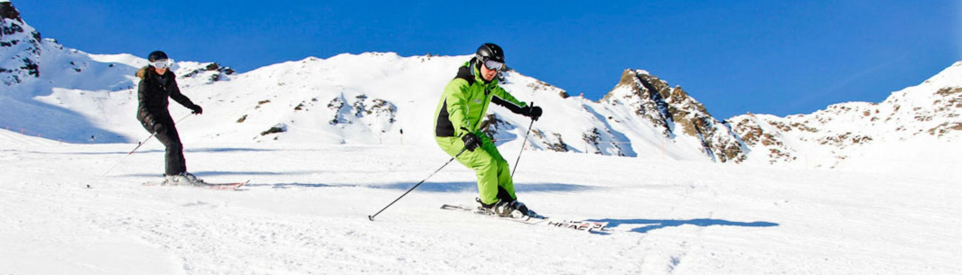 A female skier is following her ski instructor from the ski school Ski- und Bikeschule Ötztal Sölden during her Ski Lessons for Teens & Adults - All Levels.