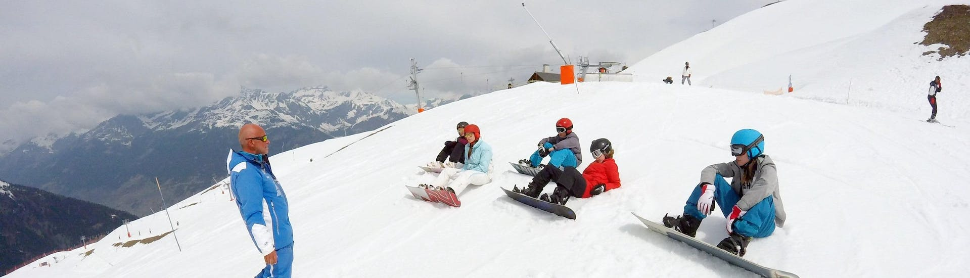 Teenagers are sitting in the snow and are listening to their snowboarding instructor during their Ski Lessons for Teens (from 13 years) - Advanced with the ski school ESI Valfréjus.