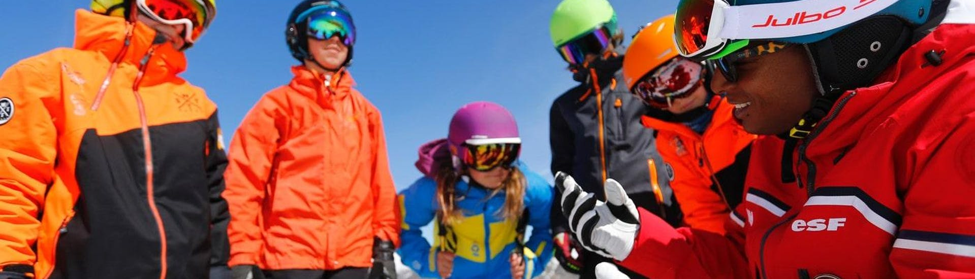 """Teens are gathered around their ski instructor from the ski school ESF Alpe d'Huez before their Ski Lessons for Teens """"Team Rider"""" (13-17 y.) - All Levels."""