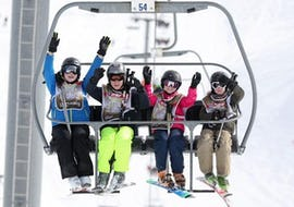 """A group of skiers is on their way to the top of the mountain with the ski lifts for their Ski Lessons for Teens """"Team Rider"""" (13-17 y.) - All Levels with the ski school ESF Alpe d'Huez."""