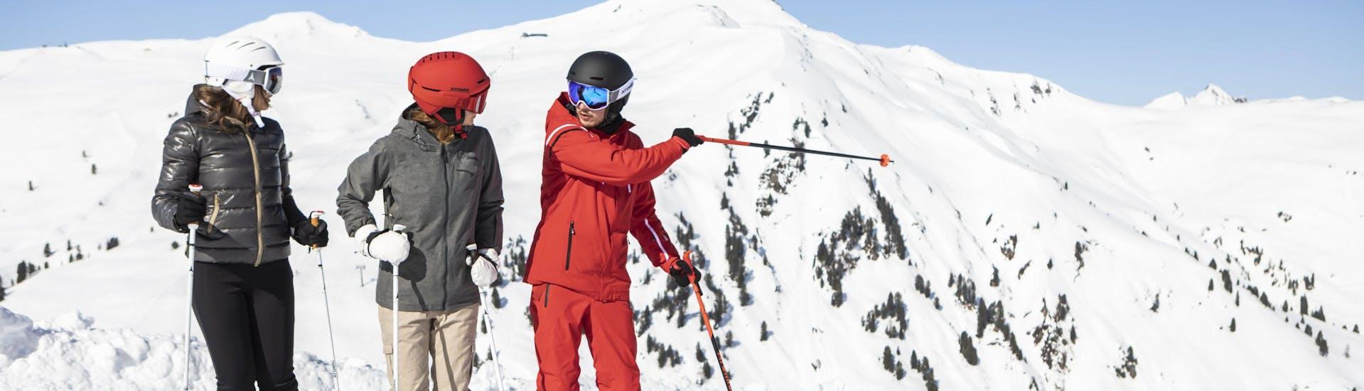 Un moniteur de ski est photographié avec deux étudiantes pendant leurs cours de ski.