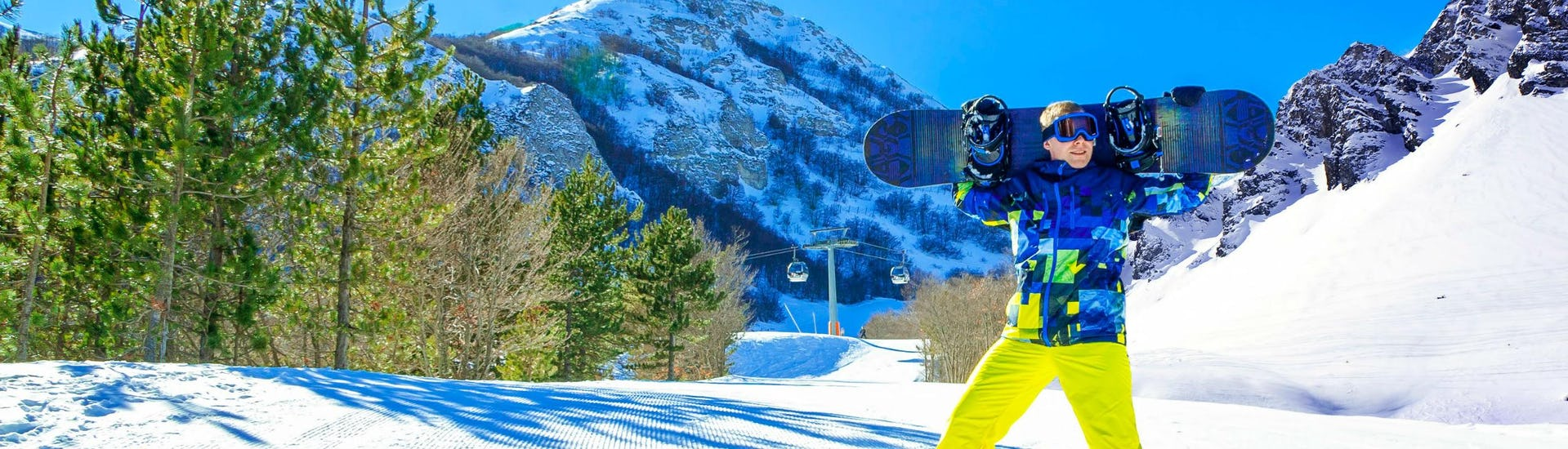 A snowboarder is posing for the camera on a sunny ski slope in the Italian region of Abruzzo, where visitors can choose from a wide range of ski lessons offered by the local ski schools.