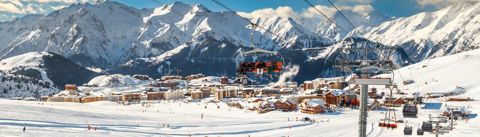 Un skieur fait une pause pendant son cours de ski pour profiter de la vue sur la station de l'Alpe d'Huez depuis les pistes.