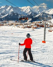 A skier is taking a break from their ski lessons to enjoy the view of the ski resort of Alpe d'Huez from the ski slope.