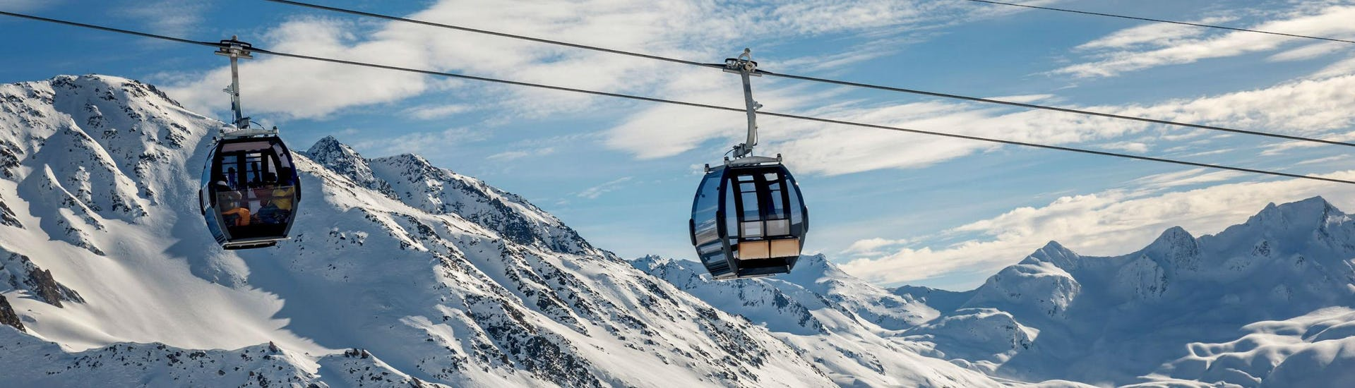 A view of the cable car carrying skiers up to the top of the mountain in the ski resort of Andermatt, where local ski schools offer a selection of ski lessons.