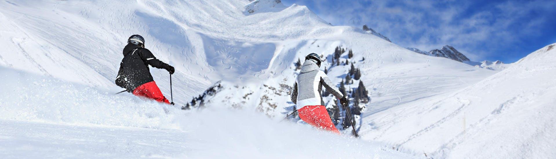 Two skiers are skiing through fresh powder snow on Arlberg, where local ski schools take aspiring skiers for their ski lessons.