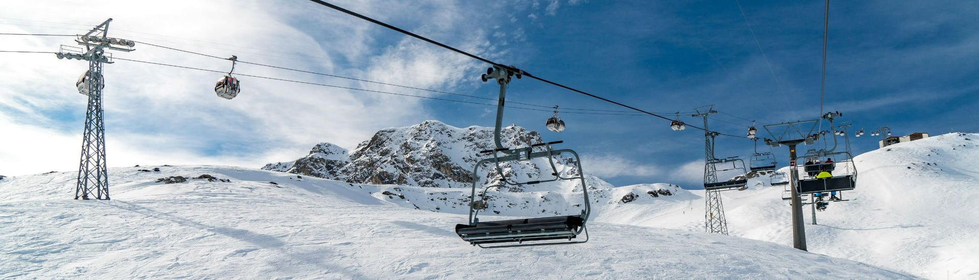 An image of a chair lift and a gondola in the Swiss ski resort of Arosa, where local ski schools offer ski lessons for all those who want to learn to ski.