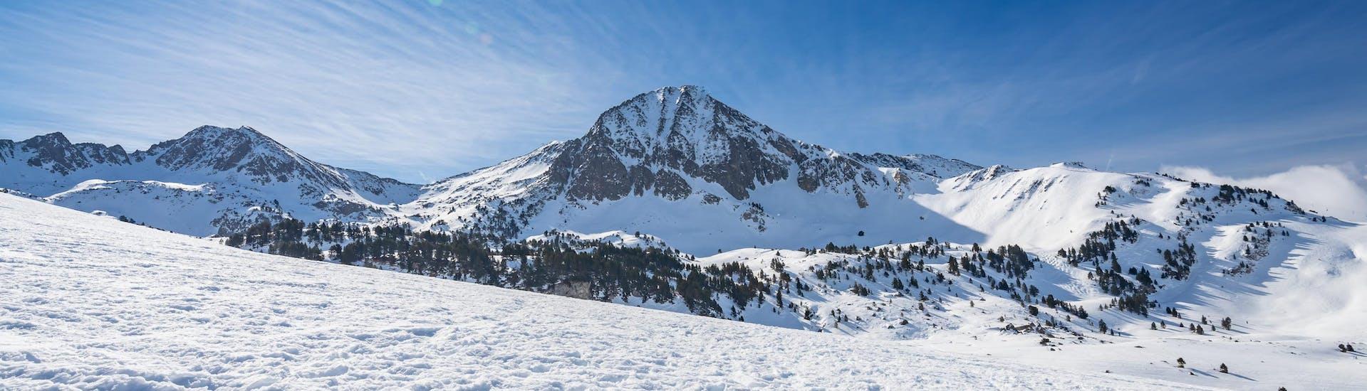 Imagen del sol brillando sobre las montañas nevadas en Baqueira, estación de esquí española done las escuelas de esquí locales ofrecen clases de esquí a los visitantes que quieren aprender a esquiar.