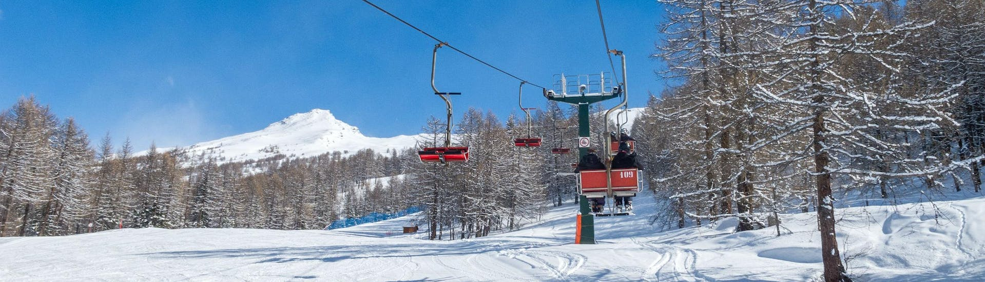 View of a ski lift transporting skiers up to the top of the mountain in the ski resort of Bardonecchia, where local ski schools offer a broad selection of ski lessons.