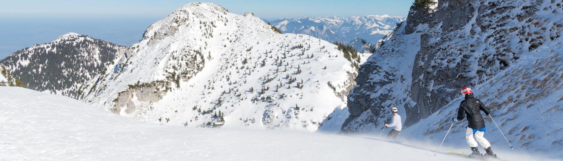 Ein Bild zweier Skifahrer auf der Skipiste in Bayrischzell - Sudefeld, einem deutschen Skigebiet wo alle, die das Skifahren lernen möchten, bei einer der örtlichen Skischulen einen Skikurs buchen können.
